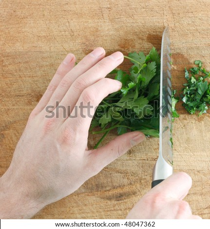 Chopping parsley on a wooden surface