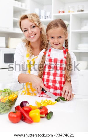 Chopping up vegetables with mom - little girl helping prepare a fresh meal - stock photo