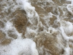 Choppy beach water is mixing with bubbling