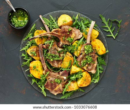Chops of lamb on bone, with baked potatoes and pesto sauce. #1033076608