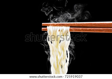 chopsticks noodles with smoke isolated on black background with clipping path