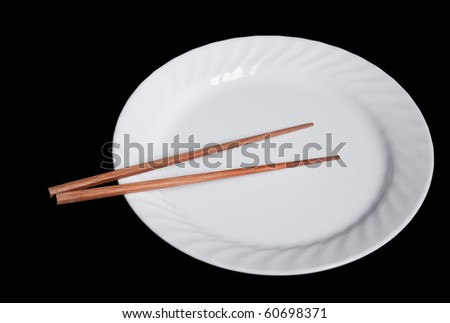 chopsticks on an empty white plate. Photographed in front of a black studio backdrop.