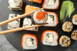 Chopsticks with delicious sushi roll, close up. Japanese food