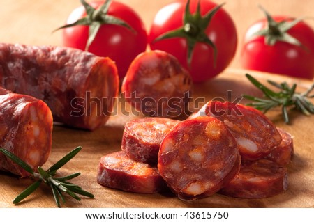 Chorizo sausage slices with rosemary herbs and tomatoes in background