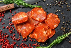 Chorizo sausage thin cut. Spanish salami with spices, paprika, pepper. Spicy food. Black background. Top view