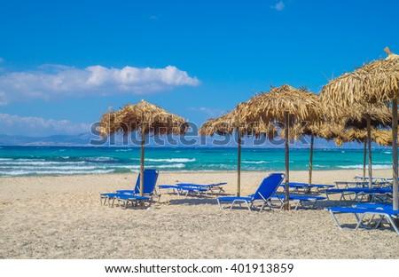 Chrisi (Chrysi) island beach background with straw sunshades, Crete, Greece. One of the most beautiful uninhabited island of Greece.
