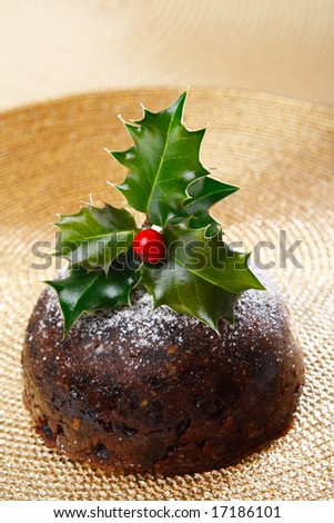 chrismas pudding with holly twig on golden background