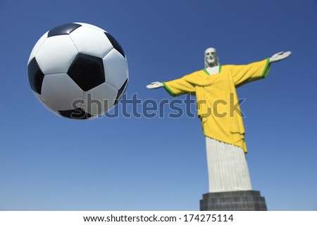 Christ the Redeemer wearing Brazil colors soccer uniform with football at Corcovado Rio de Janeiro