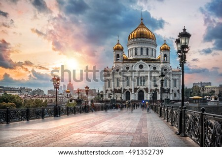 Christ the Savior Cathedral in Moscow at sunset on a background of blue rain clouds and sun