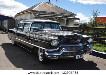 CHRISTCHURCH - MARCH 01: A classic Cadillac car parked outside an old house in Christchurch, New Zealand on March 01 2009.In NZ there are more then 13,000 vintage classic cars in immaculate condition