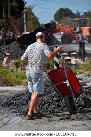 CHRISTCHURCH, NEW ZEALAND - FEBRUARY 24: Unknown man wheelbarrows earthquake liquefaction from his house on February 24, 2011 in Christchurch.
