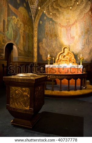 Christening font and altar in a Norwegian Protestant church at Bekkelaget in Oslo with the image of a lamb. The church is built in 1920s architecture. Shallow depth of field with the font in focus.