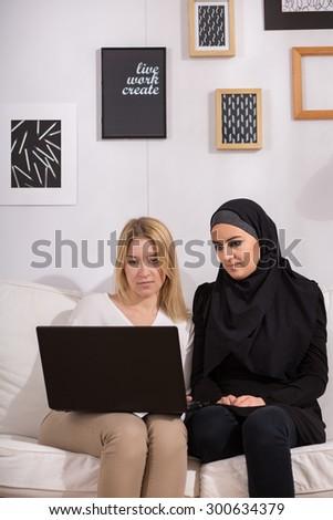 Christian and muslim girls watching film on laptop