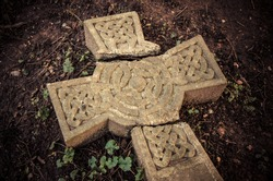 Christian beliefs - Time and traditions - Broken cross. Ancient broken Celtic cross laying on the ground at an English graveyard.