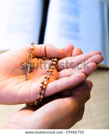 Christian believer praying to God with rosary in hand.