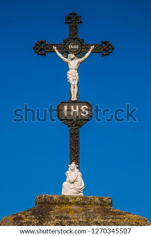 Christian black iron crucifix with white sculpture of Jesus Christ crucifixion, latin letters INRI, Iesus Nazarenus Rex Iudaeorum, Virgin Mary at the bottom of stone pedestal, sunny day, blue sky