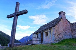 Christian Catholic cross in a small mountain stones church in the Alps  - Devero Ossola , Piedmont, Italy