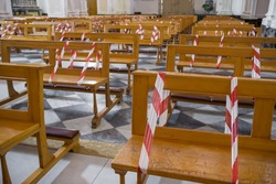 Christian church during the coronavirus pandemic Covid-19. Line strip or warning tape mark empty seats as new social distancing protection measures during pandemic of coronavirus in Italy.