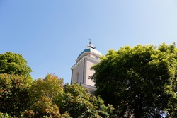 Christian church with a cross surrounded by trees. Summer day on Suomenlinna island, Helsinki, Finland