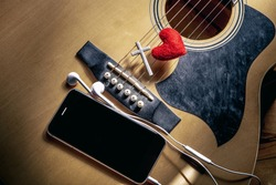 Christian cross and smart phone with red heart on acoustic guitar, christian worship concept.