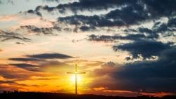 Christian cross on sunset background