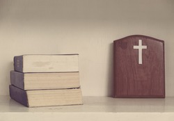 Christian cross on wood and Bible vintage effect tone.