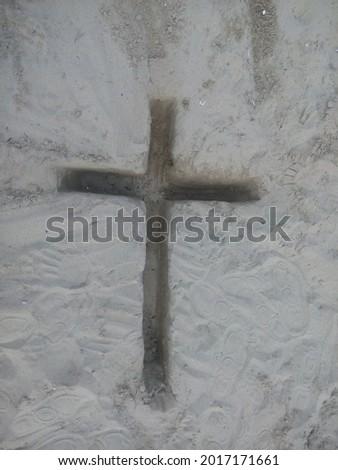 Christian cross symbol dug in sand Stock fotó ©