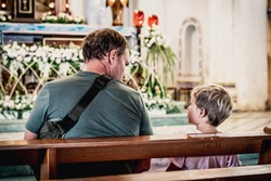 Christian dad tells child Bible story about Jesus holy people, sit in kirk. Faith religious education, modern church, father's day, responsibilities, influence on worldview, life lessons, raising boy