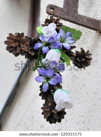 Christian Easter Cross with flowers and pine cones on the wall