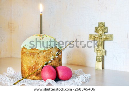 Christian Easter still life with red eggs and burning candle over the cake