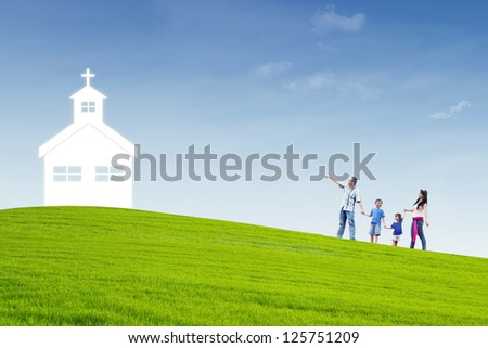 Christian family is walking to the church on top of a hill