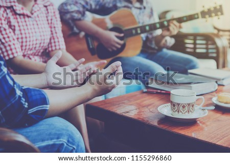 christian family worship God in home with coffee cup, Donut   and holy bible on wooden table