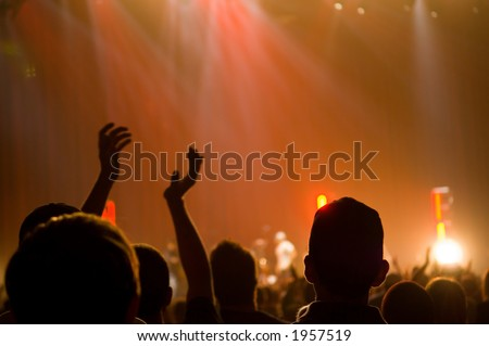 christian music concert with raised hands with one person in center clapping