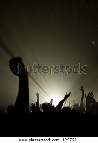 christian music concert with raised hands with one person is center worshiping