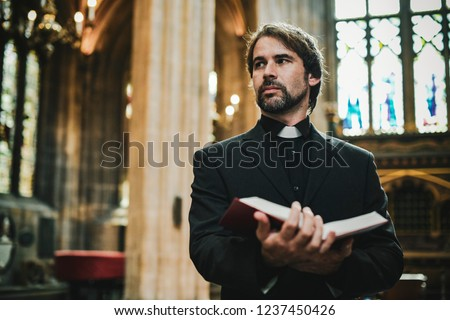 Christian priest standing by the altar #1237450426