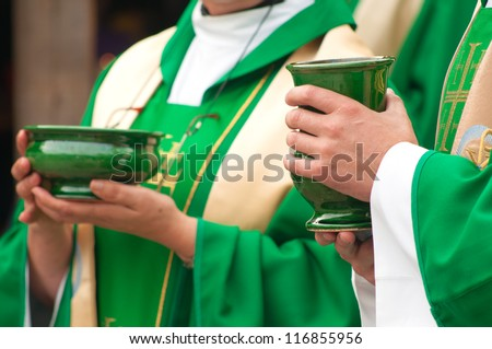 Christian priests holding bowls with wafer and wine during sacrament.