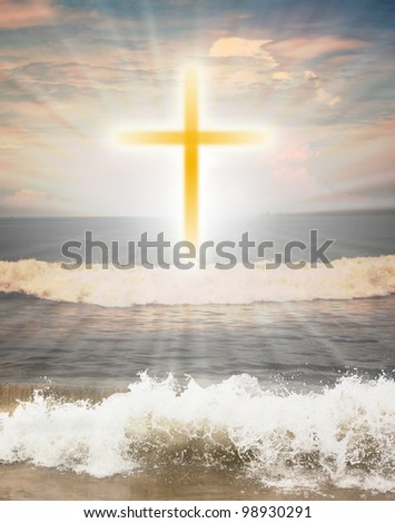 Christian religious symbol cross against sun shine  in the background and waves from the ocean in the foreground