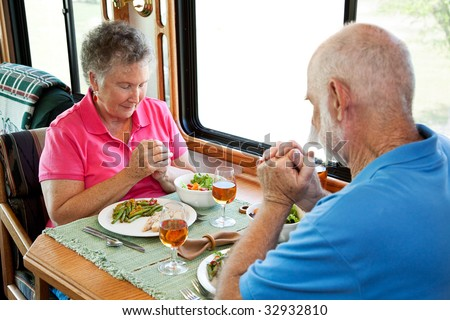 Christian senior couple saying grace over a meal in their motor home.