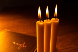 Christian sermon. A Bible and burning candles on the pastor's desk. Prayer to God. Communion with god. Religion and faith. Turning to God in prayer.