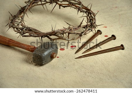 Christian symbols of the crucifixion with crown of thorns, nails and mallet on distressed cloth