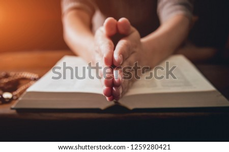 Christian woman praying in church. Hands crossed and Holy Bible on wooden desk. Background #1259280421