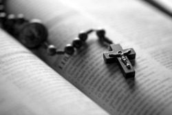Christian wooden crucifix on open bible, point focus. Religious concept image, black and white image