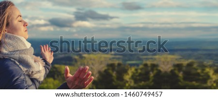 Christian worship and praise. A young woman is praying and worshiping in the evening. #1460749457