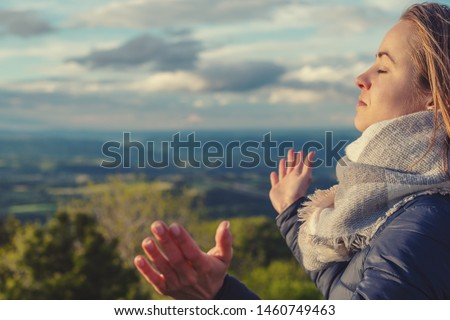 Christian worship and praise. A young woman is praying and worshiping in the evening. #1460749463