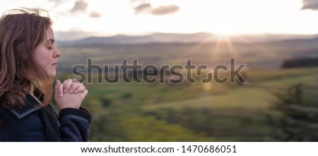Christian worship and praise. A young woman is praying and worshiping in the evening. #1470686051