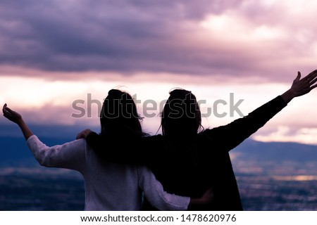 Christian worship and praise. Two young woman are praying and worshiping in the evening. #1478620976