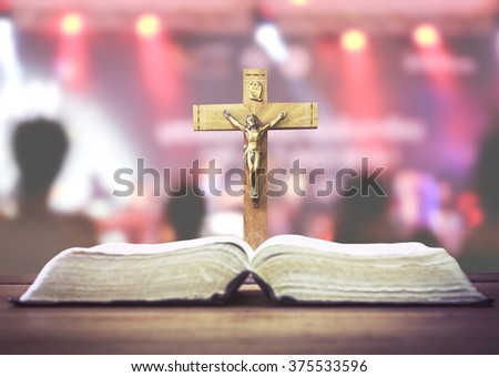 Christian worship, wooden cross with crucifix of Jesus Christ with burred image of people in music concert, focus on the crucifix, Christian concept of worship