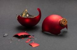 Christmas accident. Red Christmas ball broken, dark gray background, closeup view