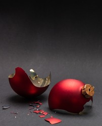 Christmas accident. Red Christmas ball broken, dark gray background, closeup view, copy space
