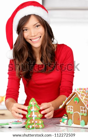 Christmas activities - girl making gingerbread house. Young woman in Christmas preparations putting icing on gingerbread house. Model wearing santa hat.